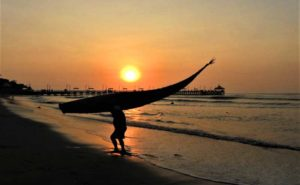 Man hauling Totora reed raft at sunset in Peru