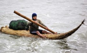 Man rowing his Totora reed raft in Peru